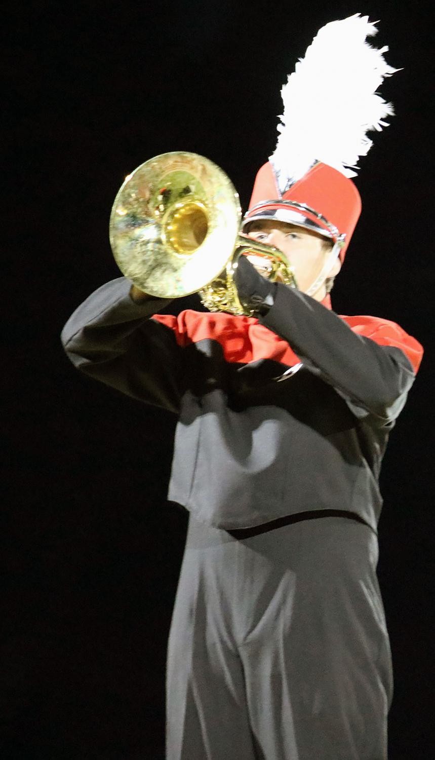 Senior marching band member, Adam Richling (18), climbs the stage and plays a mellophone solo during the song