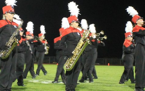 Molly Byrne (18), Demi Ball (16), and Tristan Brady (17) march onto the field for the varsity game's halftime show on Aug. 29, 2014.