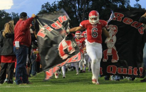 Nick Schreiber (15) Breaks through the banner at the season opener.