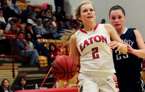 Bailey Schumacher (16) drives down the court with a University player close behind.
