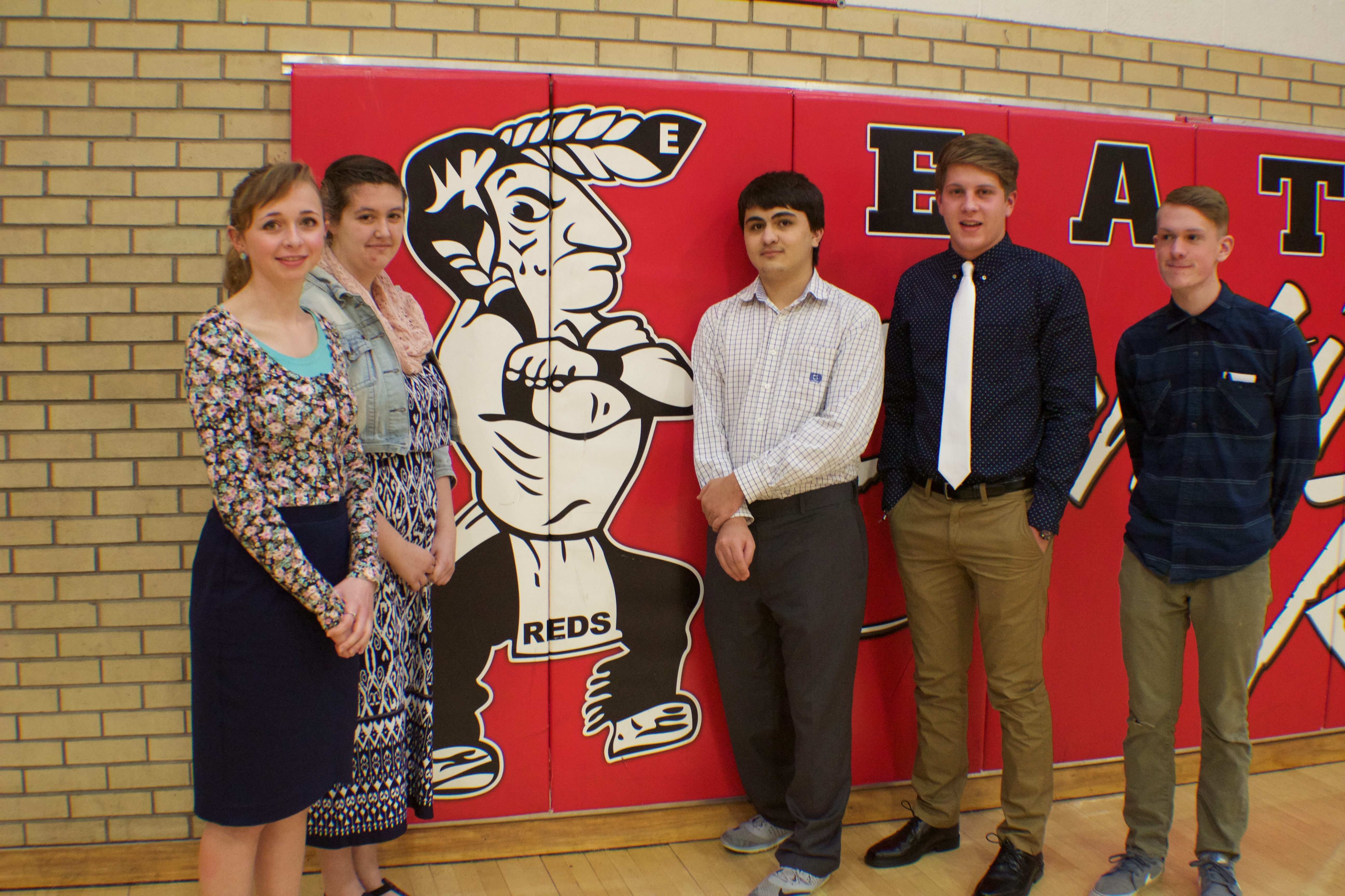 Red Ink members stand next to the mascot (left to right, Karalee Kothe(16), Sarah Jakel (17), Isaiah Cordova (17), Devan McKenney (17), and Cameron Moser (17)