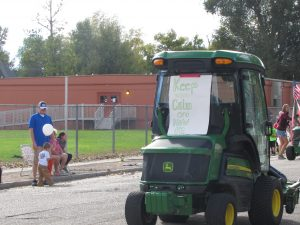 """Maintenance man Flor drives his lawn mower through the parade with a sign that reads, """"Keep Calm and Mow On."""""""