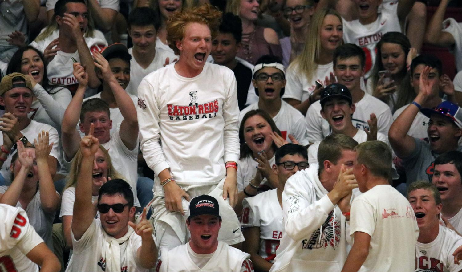 With all students dressed for a white-out, CJ Baskowski (18) jumps out of his seat to celebrate a Ma