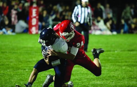 Fullback Jesse Mongan makes an open field tackle against a Timberwolf player. Mongan had two tackles  on the evening helping the Reds defense completely disable Pinnacle's