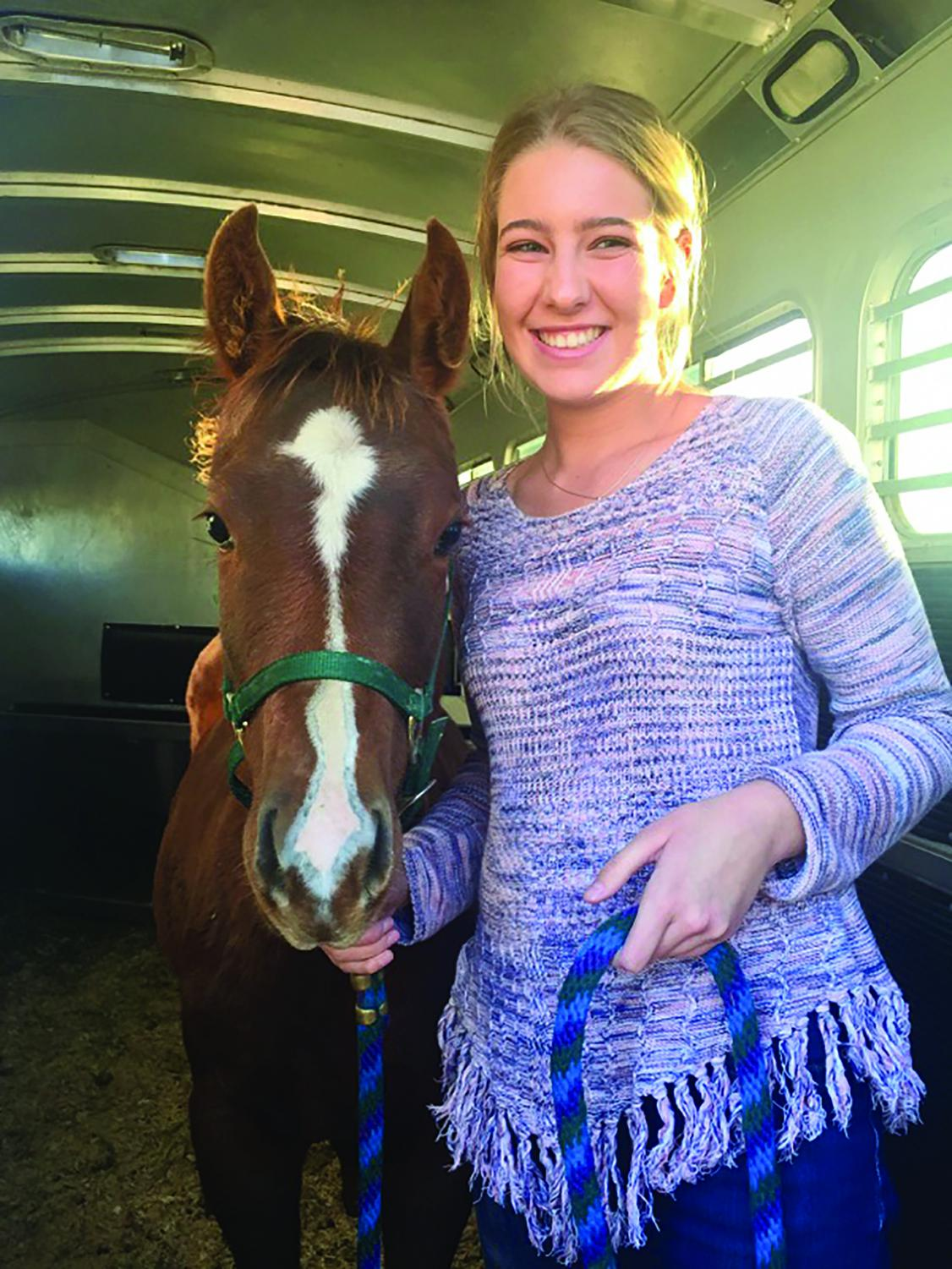 Lauren Weaber standing in the trailer with her new filly, Ivy.