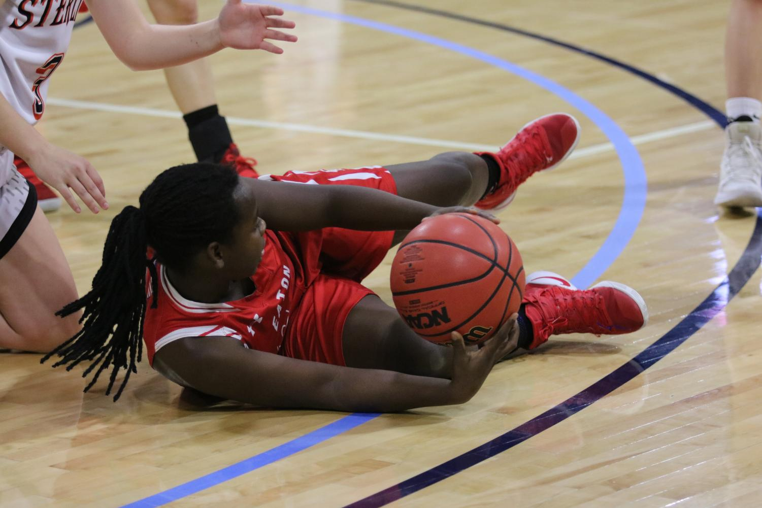 Addie Randel dives on the floor to retrieve a loose ball, surrounded by Resurrection players.