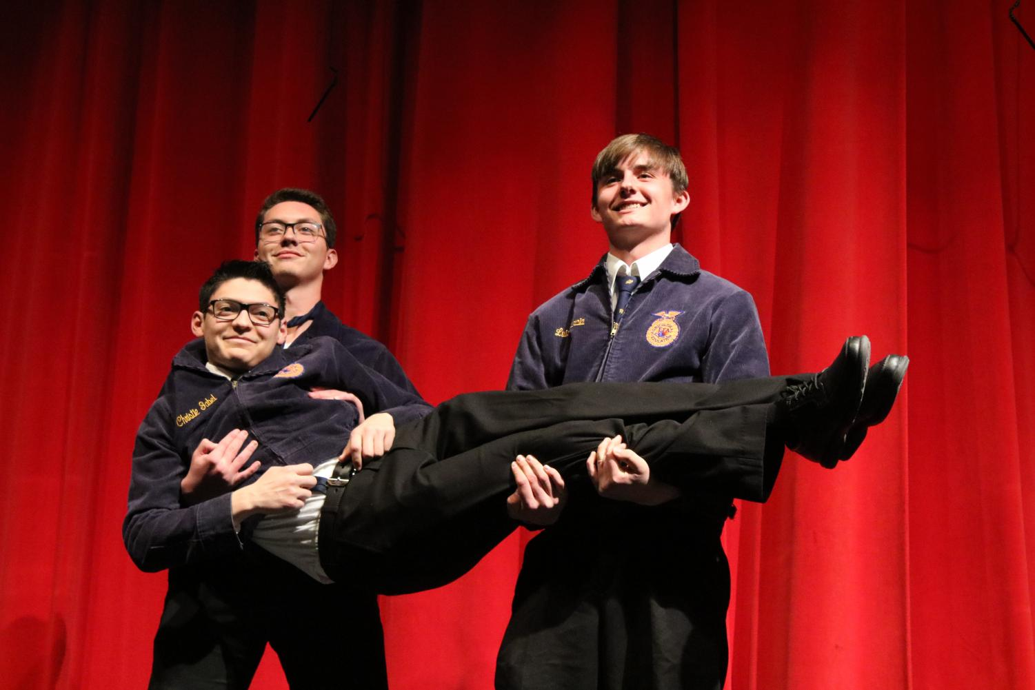 Seniors Jesse Mongan and Matthew Jones carry out Neo Orosco on stage to flex their muscles for buyers.