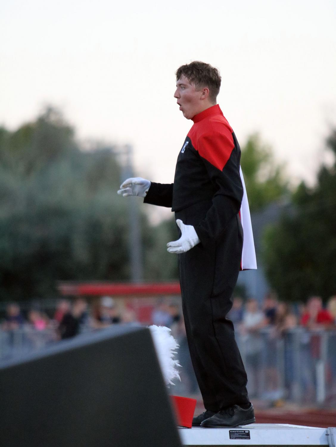 Colton Sell (20) stands on a step ladder before masses of people as he directs the marching band during their performance