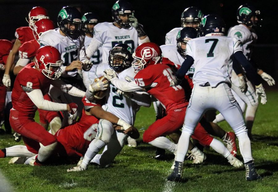 The Reds defensive players, Javi Hernandez (20), Ty Garnhart (19) and Danny Chavez (19) tackle the Wildcats running back.