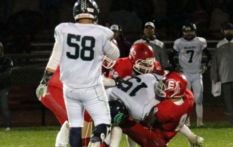 Seniors Ty Garnhart (19) and Danny Chavez (19) tackle a player from The Academy