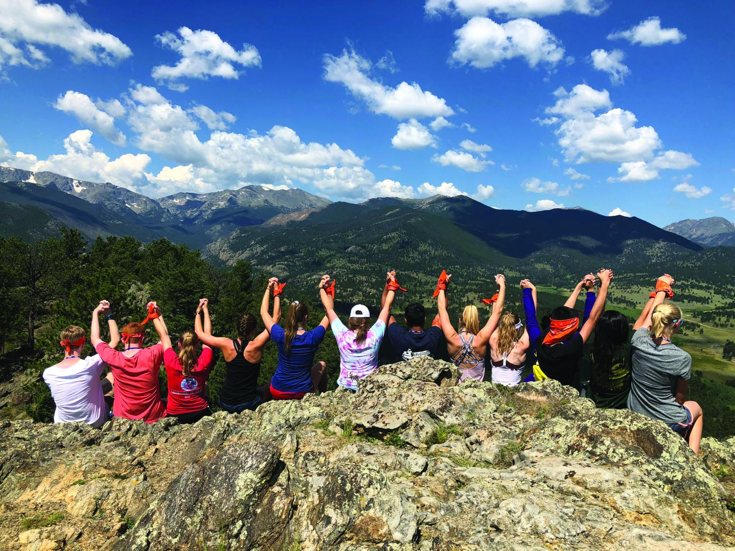 Conferees raise arms in victory after tackling a team building hike at the YMCA of the Rockies. Climbers scaled the mountain wearing symbolic orange bandanas on their wrists.