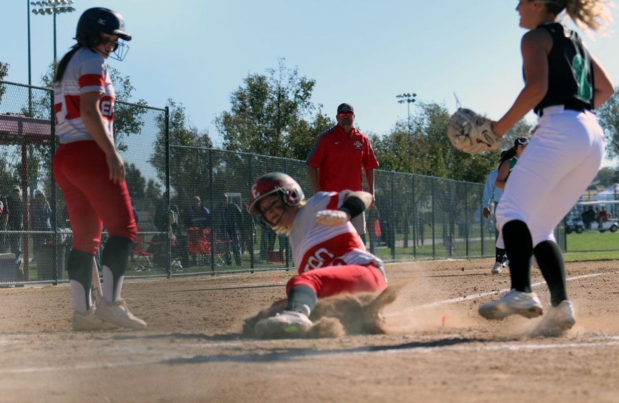 Tristian Brandley (18) slides home to score a point for the Reds