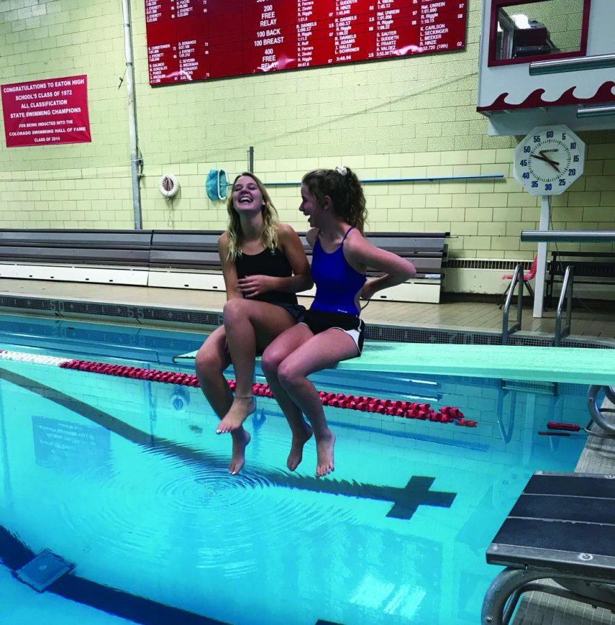 Clarise Sviatko and Jamie Bulzomi laugh while sitting on the diving board.