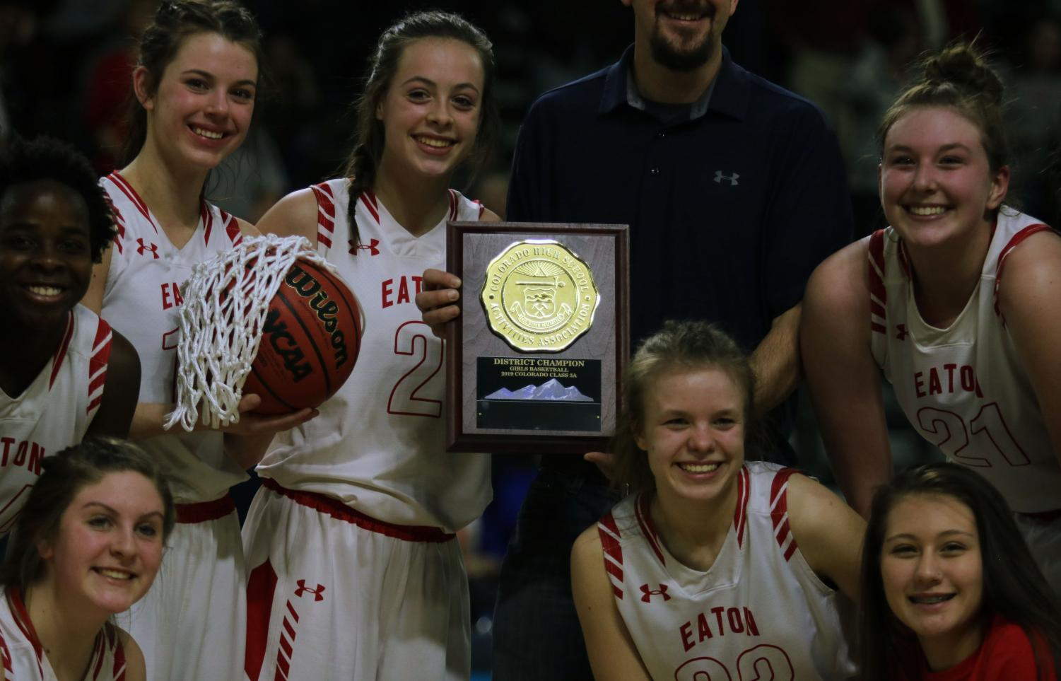 Moments after the district championship win, teammates Addie Randel, Nakaiya Kuskie, Gracie Schrebier, Bailie Duncan, Michaela Hill, Sydney Booth, and Anya Womack gather around the plaque.
