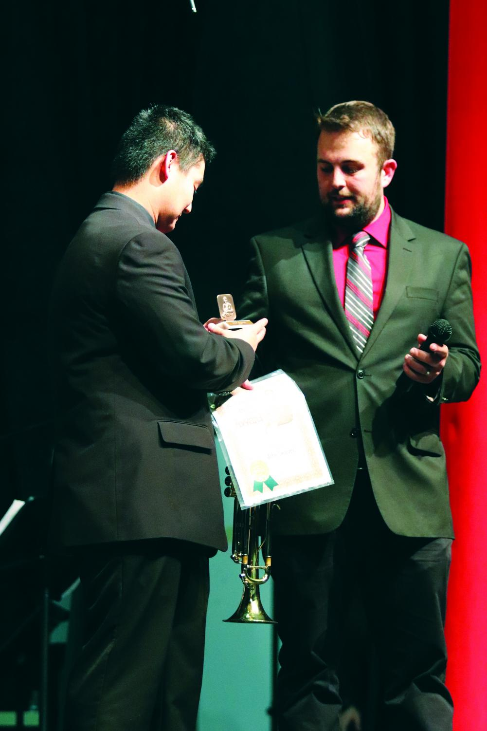 Band director Logan Doddridge hands John Seaver his Louis Armstrong Award