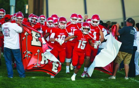 The Reds break through the banner as they run onto the field for their home game against D'Evelyn.