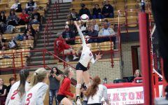 Sydney Leffler (21) jumps and hits the ball for the kill.
