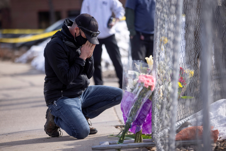 Conrad Wright leaves flowers and takes a moment at the site of a mass shooting at King Soopers grocery store, in Boulder, Colorado, U.S., March 23, 2021.  REUTERS/Alyson McClaran     TPX IMAGES OF THE DAY