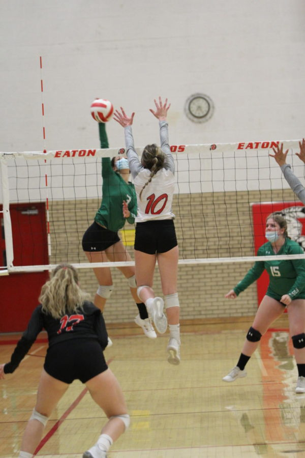 Sydney Leffler (21) jumps up to block the ball.